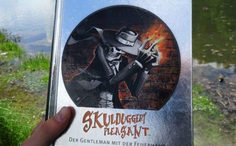 """""""Skulduggery Pleasant - Der Gentleman mit der Feuerhand"""" vor einem Bergsee."""