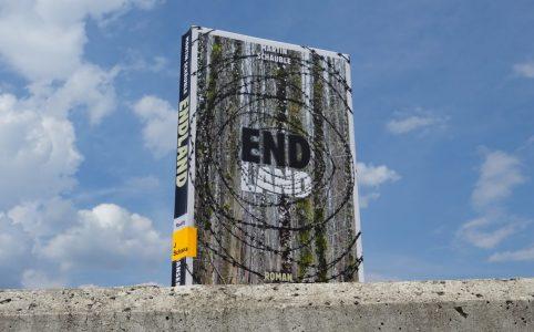 """Das Buch """"Endland"""" steht auf einer Betonmauer."""