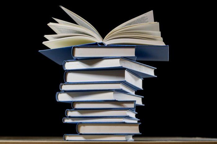 Ein Stapel Bücher vor schwarzem Hintergrund.