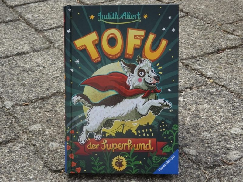 """Das Buch """"Tofu, der Superhund"""" steht auf Pflastersteinen."""